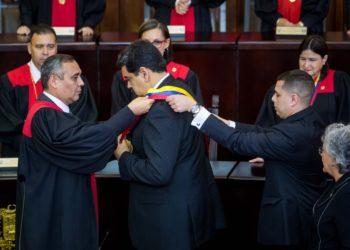 """CR01. CARACAS (VENEZUELA), 10/01/2019.- El presidente de Venezuela, Nicolás Maduro (c), reacciona luego de jurar como presidente para un segundo período de gobierno que lo mantendrá en el poder hasta el año 2025, ante el presidente del Tribunal Supremo de Justicia (TSJ), Maikel Moreno (i), durante una ceremonia hoy, jueves 10 de enero de 2019, en Caracas (Venezuela). El mandatario tomó juramento ante el Tribunal Supremo de Justicia (TSJ), en Caracas, acompañado por otros seis jefes de Estado que fueron los únicos en asistir a este acto señalado por opositores y buena parte de la comunidad internacional como el inicio de la """"usurpación"""" de la Presidencia de Venezuela. Tras seis años en el poder a Maduro lo cuestiona no solo la población, que durante su mandato ha visto cómo el país se ha sumido en la peor crisis económica de su historia, también gobiernos de América y Europa que han mostrado su preocupación por las condiciones en las que se encuentra Venezuela. EFE/Miguel Gutiérrez"""