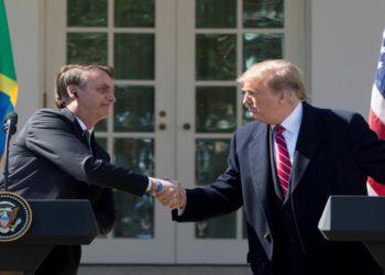 """MRX03. WASHINGTON (ESTADOS UNIDOS), 19/03/2019.- El presidente de Estados Unidos, Donald Trump (d), estrecha la mano de su homólogo brasileño, Jair Bolsonaro (i), tras la reunión mantenida entre ambos mandatarios en la Casa Blanca, este martes en Washington (Estados Unidos). Trump aseguró que se siente """"honrado"""" por las comparaciones con Bolsonaro y afirmó que evaluará """"muy en serio"""" la idea de dar a Brasil privilegios militares similares a los que reciben los aliados estadounidenses miembros de la OTAN. EFE/ Michael Reynolds"""