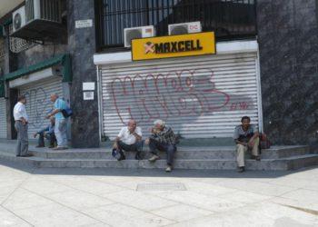 AME1310. CARACAS (VENEZUELA), 26/03/2019.- Varias personas conversan a las afueras de locales comerciales cerrados debido a un apagón este martes, en Caracas (Venezuela). Los cortes de luz aún persisten en algunas zonas de la capital venezolana. EFE/ Rayner Peña
