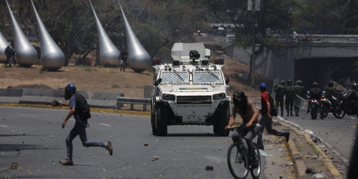 AME6879. CARACAS (VENEZUELA), 30/04/2019.- Simpatizantes del presidente de la Asamblea Nacional, Juan Guaidó, protestan frente a una tanqueta durante una manifestación en apoyo a su levantamiento contra el gobierno de Nicolás Maduro este martes, en la zona de Altamira, en Caracas (Venezuela). El jefe del Parlamento venezolano, Juan Guaidó, se levantó junto a un grupo de militares contra el gobierno de Nicolás Maduro. EFE/ Miguel Gutiérrez